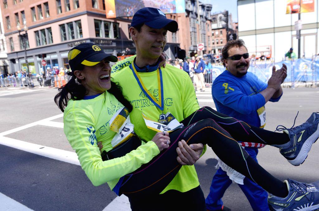 2013 Boston Marathon bombing survivor Doug Julian (R) carries fellow survivor Lynn Crisci over the marathon finish line during a Tribute Run for survivors and first