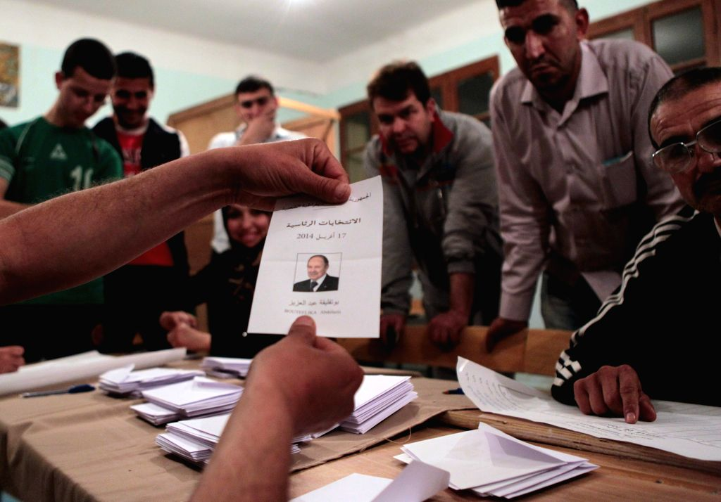 Organizers, monitors and represisentatives of the six presidential candidates count ballots at a polling station in Lakhdaria, Bouira Province, April 17, 2014. ...