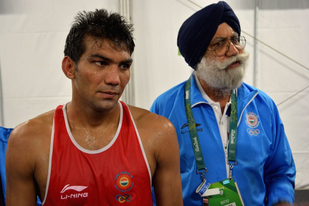 Boxer Manoj Kumar and Indian boxing head coach Gurcharan Singh Sandhu talking to reporters after Kumar beat Evaldas Petrauskas of Lithuania in the men\'s Light Welterweight (64kg) category at the ... - Manoj Kumar and Gurcharan Singh Sandhu