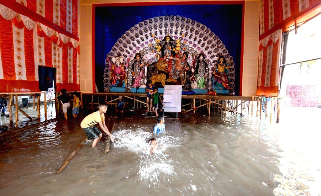 Boys enjoy themselves after heavy rains cause floods in Kolkata, on 29 Sep, 2019.