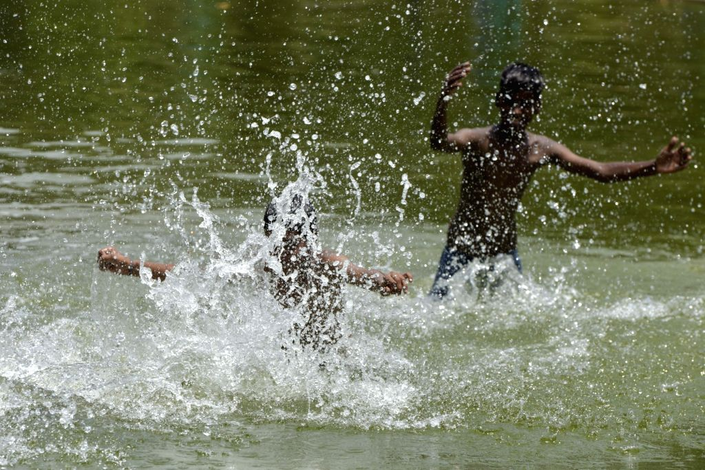 Boys enjoy themselves at a pond on a hot summer day, near India Gate in New Delhi, on June 4, 2019.
