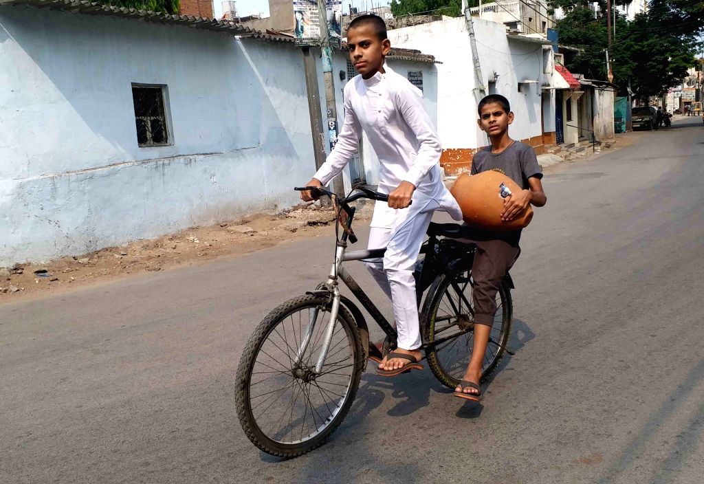 Boys paddle through a deserted Hyderabad street as they return home with an earthen pot that helps to keep water stay cool for long as the temperatures go up in the city during the ...