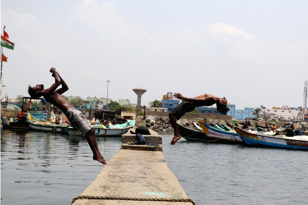 Boys take a plunge into the water at Kasimedu fishing harbour to get respite from the heat on a hot sunny day, in Chennai on May 21, 2018.