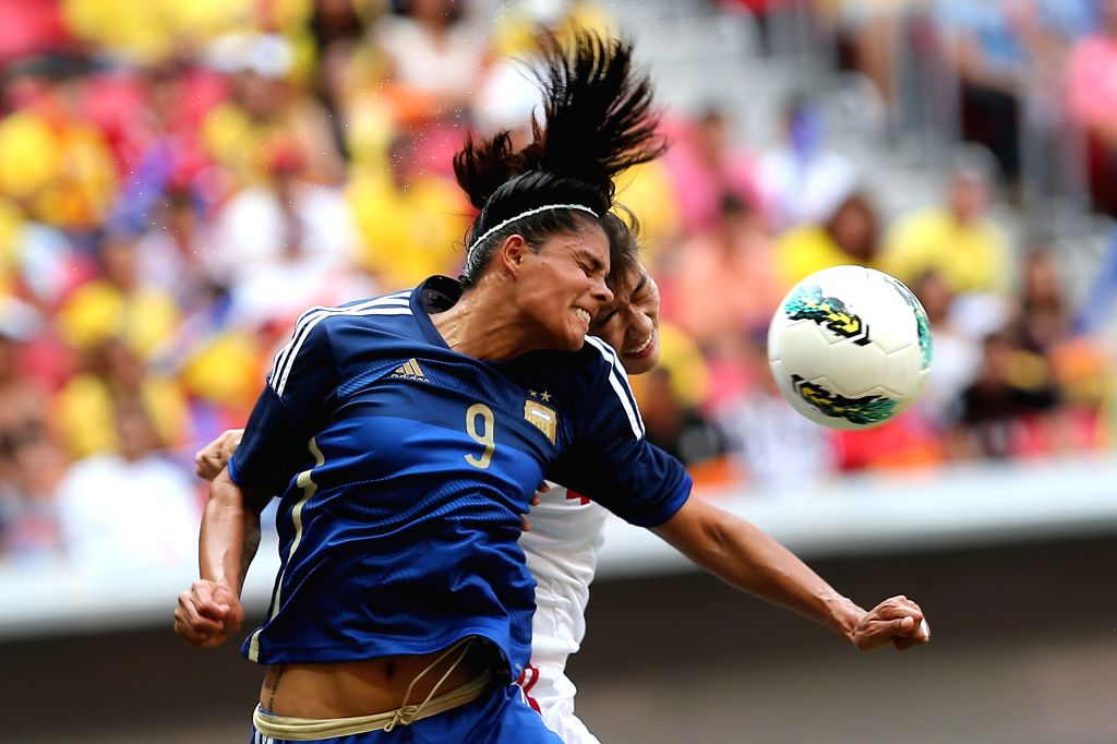 China's Li Jiayue (back) heads the ball with Argentina's Florencia Jaimes during a match between China and Argentina of the 2014 International Women's Football ...