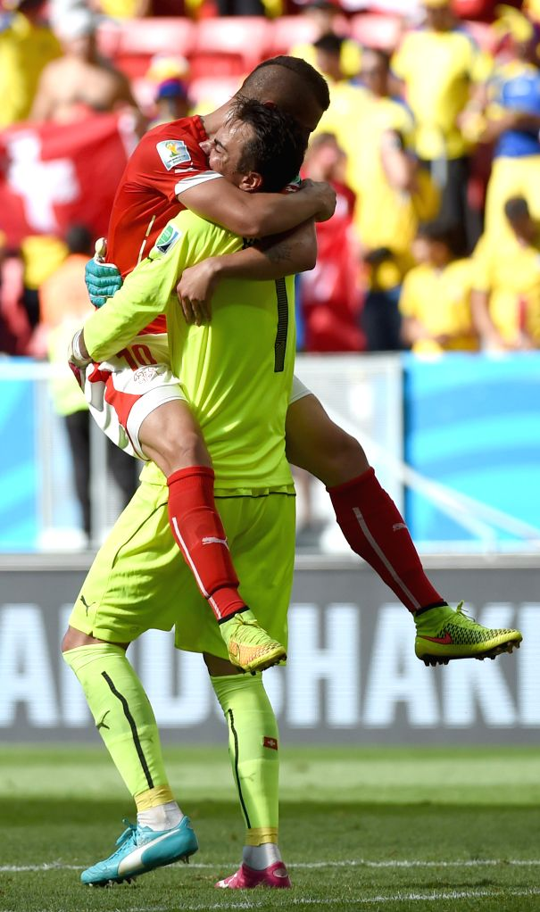 Switzerland's Granit Xhaka (L) embraces with goalkeeper Diego Benaglio as a way of celebrating for the victory after a Group E match between Switzerland and ...