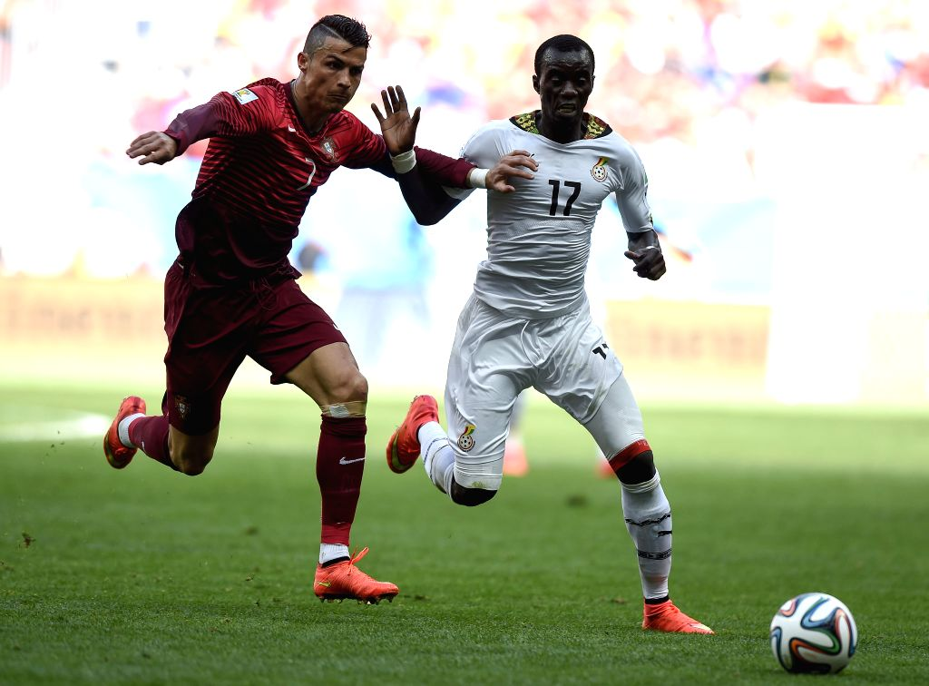 Portugal's Cristiano Ronaldo (L) vies with Ghana's Mohammed Rabiu during a Group G match between Portugal and Ghana of 2014 FIFA World Cup at the Estadio Nacional .