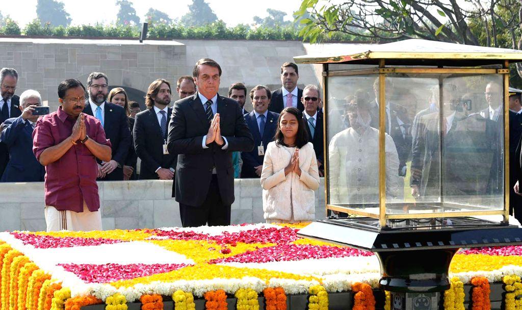 Brazilian President Jair Bolsonaro pays homage at the Samadhi of Mahatma Gandhi at Rajghat, in New Delhi on Jan 25, 2020. Also seen MoS External Affairs and Parliamentary Affairs V. ...