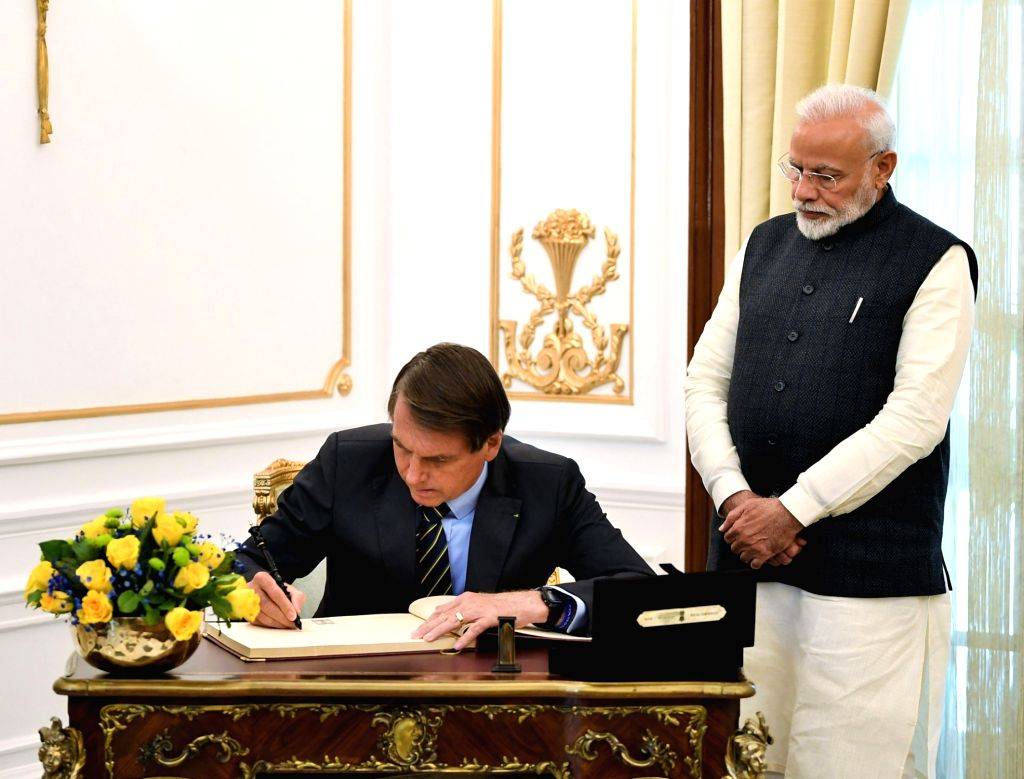 Brazilian President Jair Messias Bolsonaro signs the visitors' book of Hyderabad House as Prime Minister Narendra Modi looks on, in New Delhi on Jan 25, 2020. - Narendra Modi