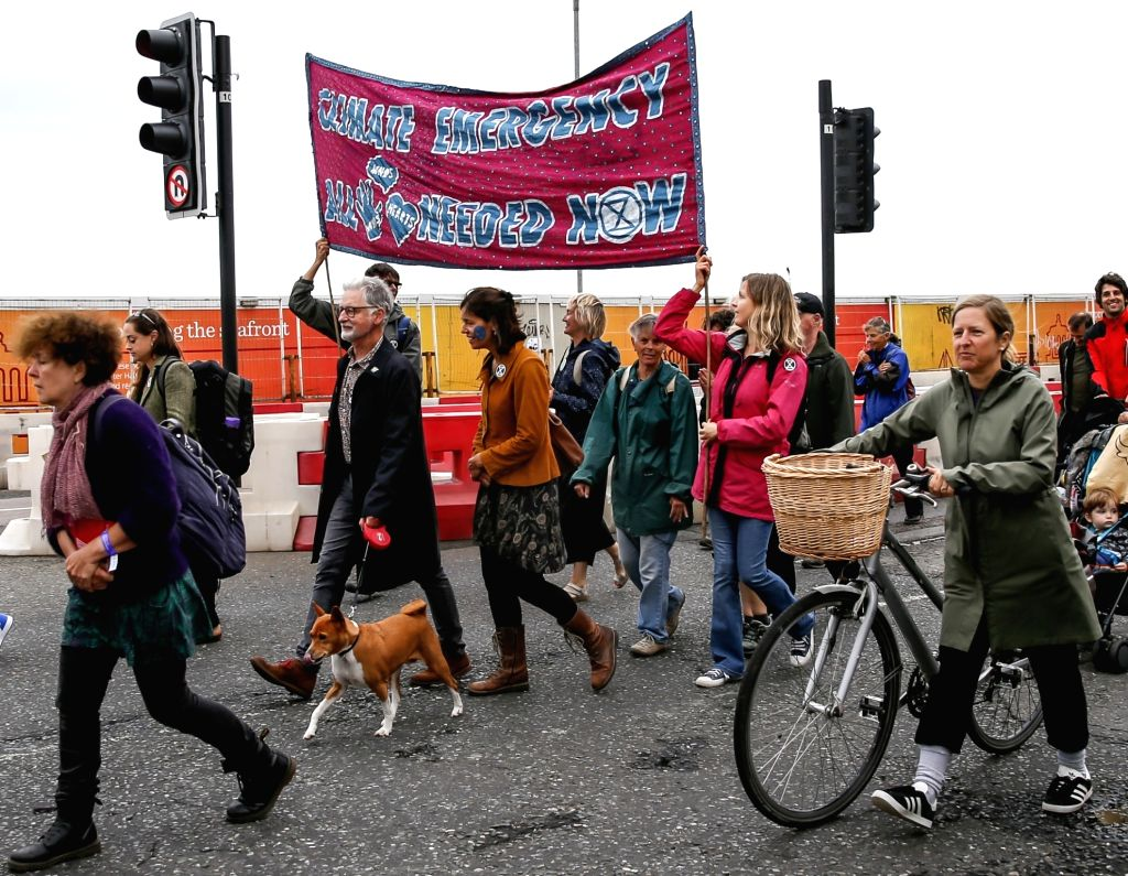 BRIGHTON, Sept. 22, 2019 - People hold banners and placards during a march calling for action against climate change in Brighton, Britain on Sept. 22, 2019.