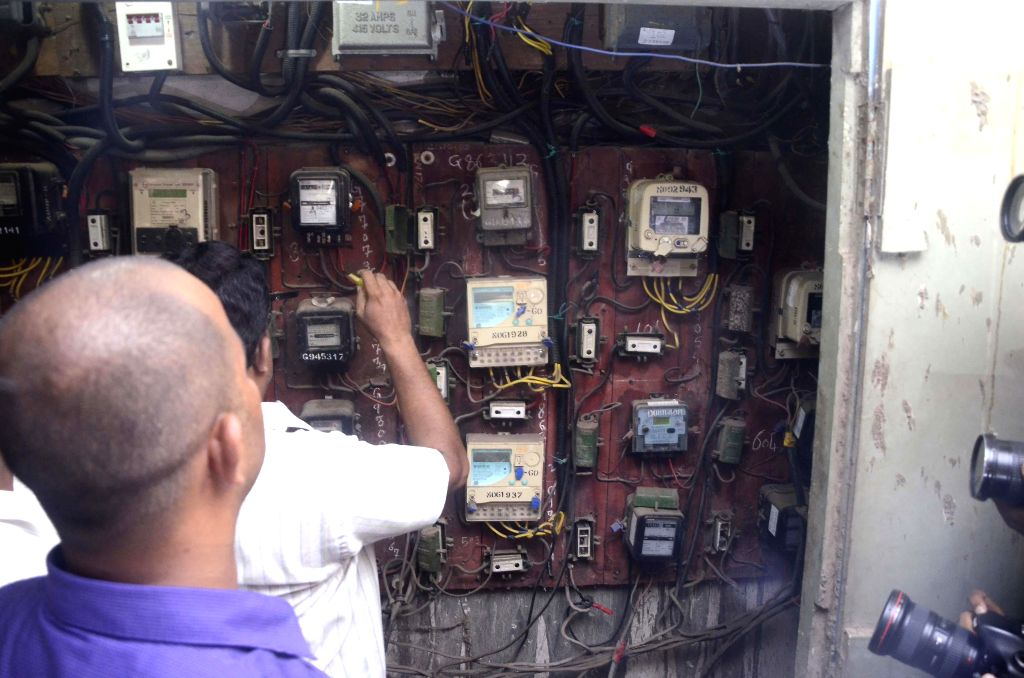 Brihanmumbai Municipal Corporation (BMC) personnel disconnect electricity supply to the apartments inside Campa Cola Compound in Mumbai on June 23, 2014.