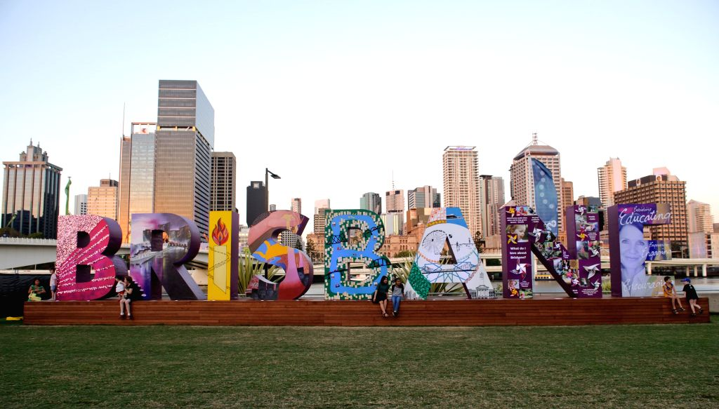 """People sit by the """"Brisbane"""" sign near the Brisbane Convention and Exhibition Centre in Brisbane, Australia, Nov. 14, 2014. World economic leaders will travel to Brisbane for the ."""