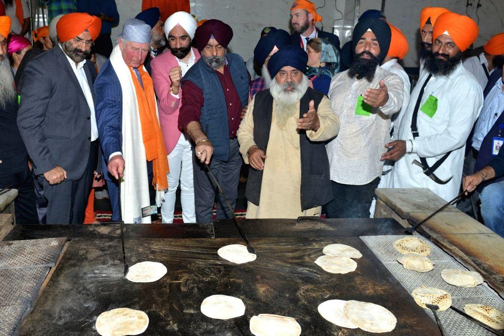 Britain's Prince Charles helps in preparing chapattis as part of 'Kar seva' during his visit to Sri Bangla Sahib Gurudwara during the 550th birth anniversary celebrations of Guru Nanak ... - Nanak Dev