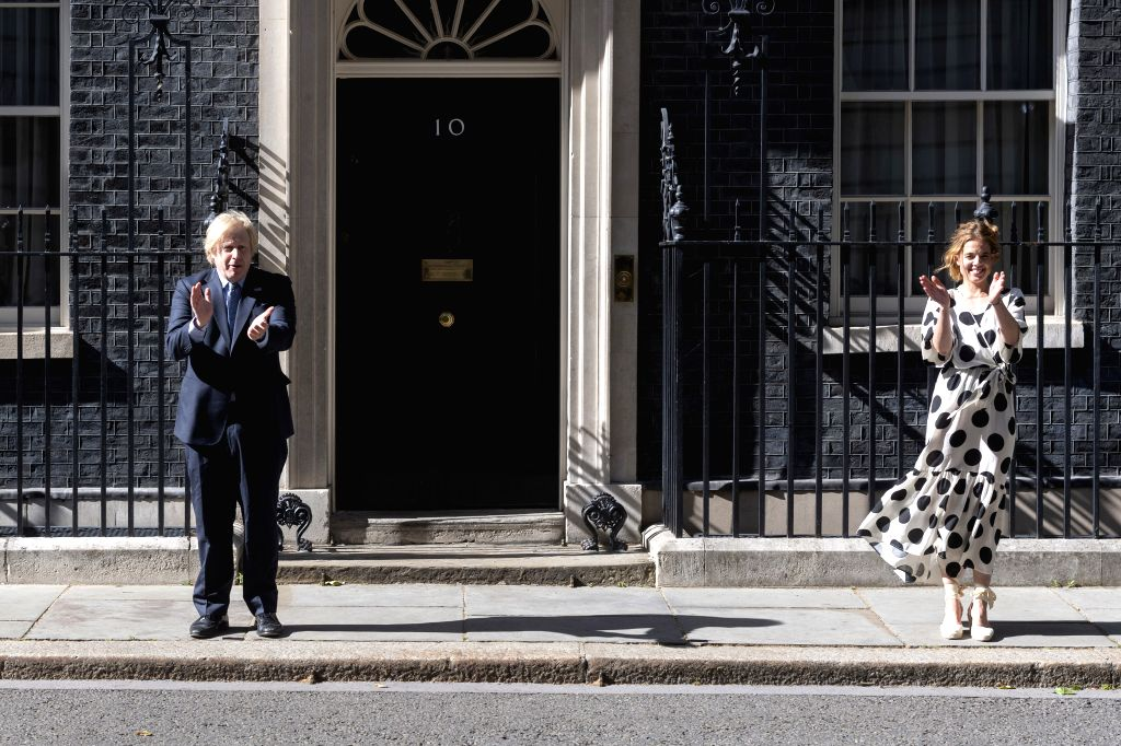 """British Prime Minister Boris Johnson (L) and founder of """"Clap for Carers"""" Annemarie Plas clap outside 10 Downing Street to mark the 72nd anniversary of the ... - Boris Johnson"""