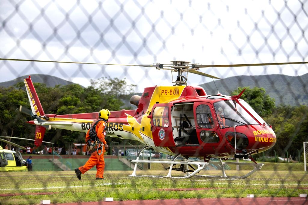 BRUMADINHO, Jan. 27, 2019 - A fireman walks by a rescue mission helicopter in a helping center near Brumadinho, the state of Minas Gerais, Brazil, on Jan. 26, 2019. At least 34 people were killed ...