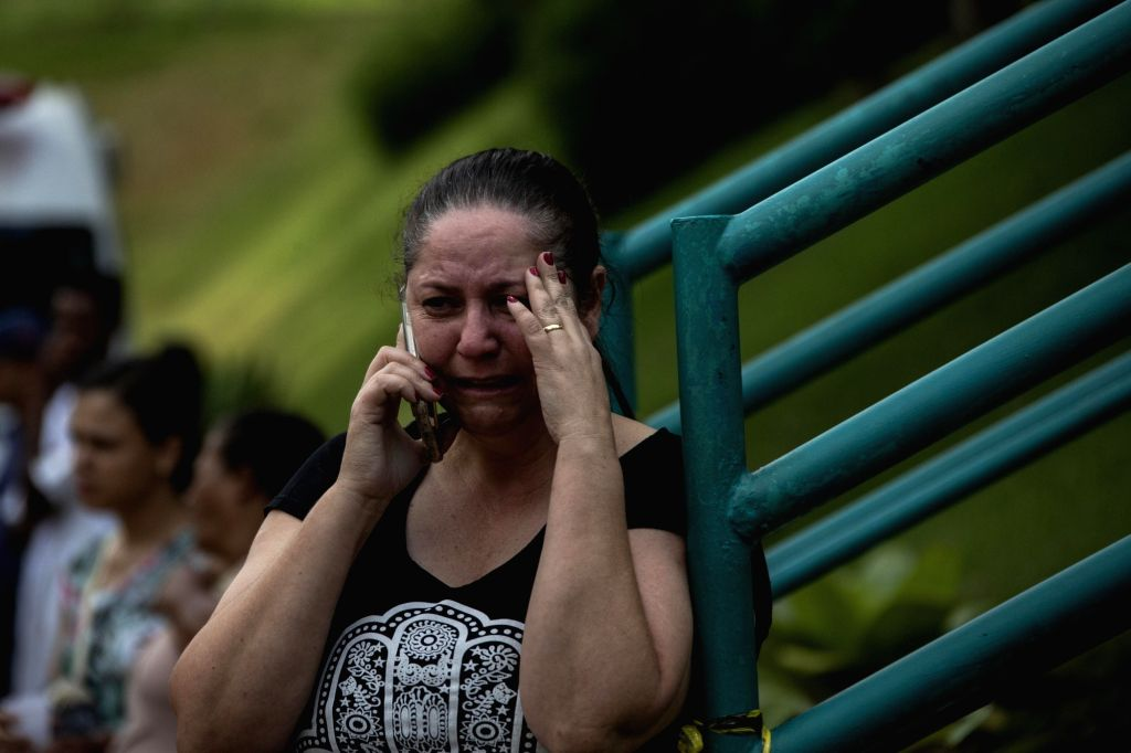 BRUMADINHO, Jan. 27, 2019 - A woman makes a call as she cries in a helping center near Brumadinho, the state of Minas Gerais, Brazil, on Jan. 26, 2019. At least 34 people were killed after a tailings ...