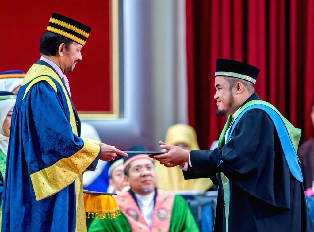 Brunei's Sultan Haji Hassanal Bolkiah (L, front) presents a certificate to a student during the University Brunei Darussalam (UBD)'s 28th Convocation in ...