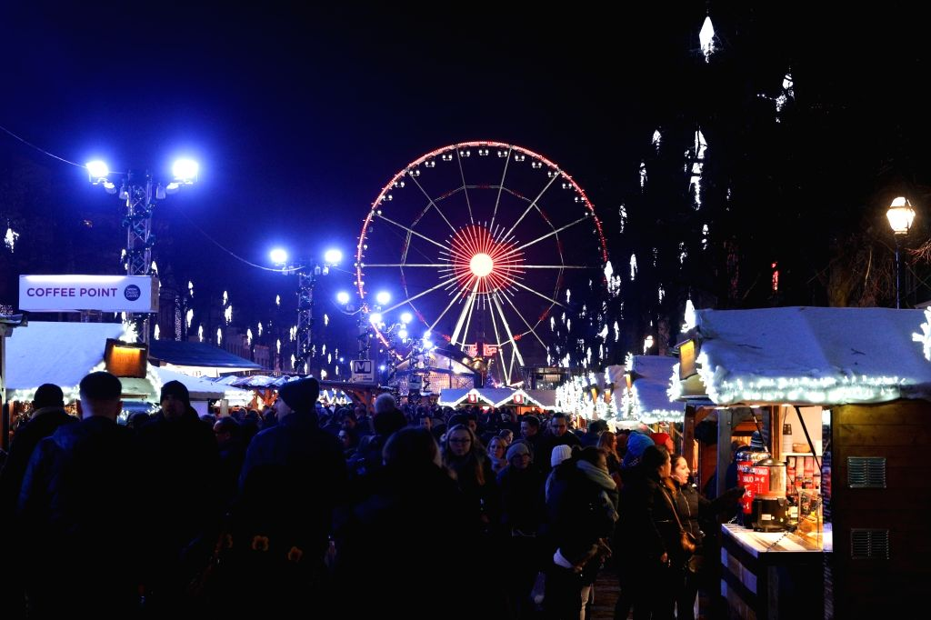 BRUSSELS, Dec. 12, 2018 - People visit a Christmas market in central Brussels, Belgium, on Dec. 12, 2018. More than 200 chalets and fairground attractions at the Christmas market attract visitors ...