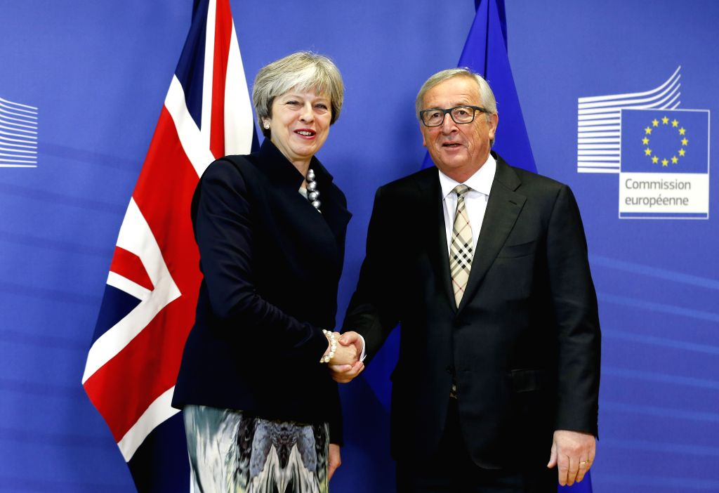 BRUSSELS, Dec. 4, 2017 - European Commission President Jean-Claude Juncker (R) greets British Prime Minister Theresa May prior to a Brexit negotiation meeting at EU headquarters in Brussels, Belgium, ... - Theresa May
