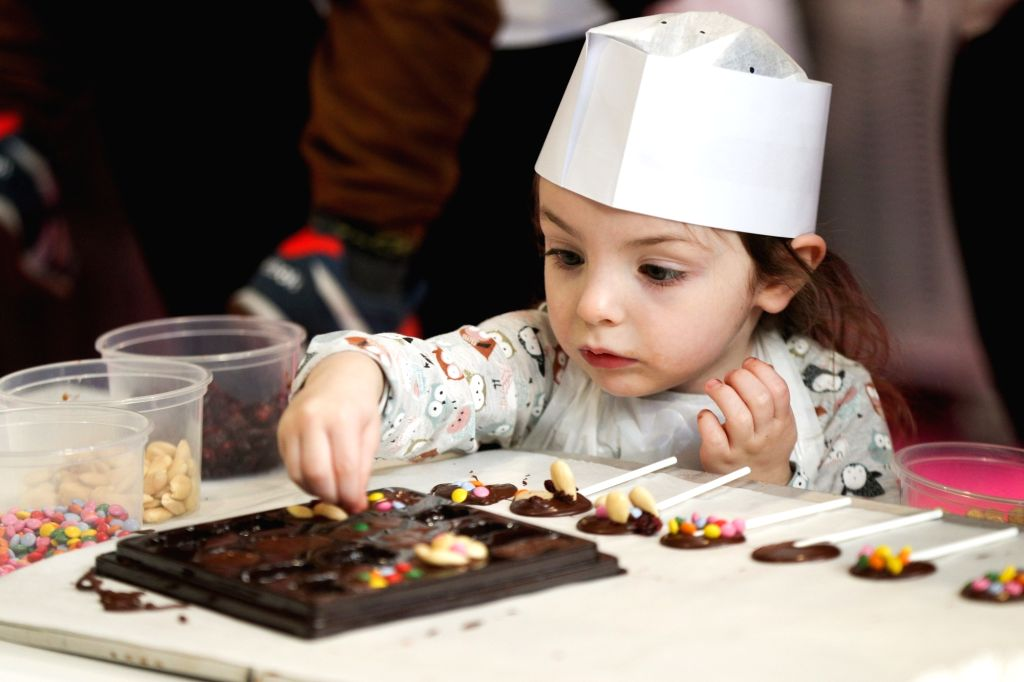 BRUSSELS, Feb. 22, 2019 - A girl makes chocolates at the 6th edition of the Chocolate Fair in Brussels, Belgium, on Feb. 22, 2019. The 6th edition of the Chocolate Fair (Le Salon du Chocolat) kicked ...