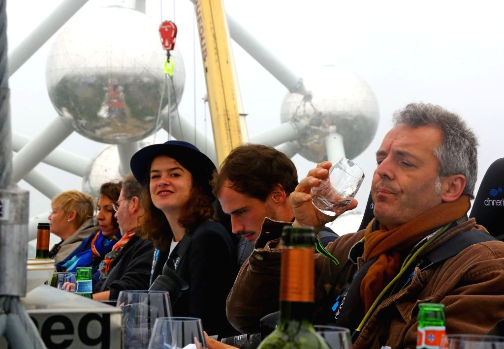 "BRUSSELS, June 2, 2016 - Guests sit at a table suspended from a crane at a height of 50 meters in front of the Atomium during the 10th anniversary of the event ""Dinner in the Sky"" in ..."