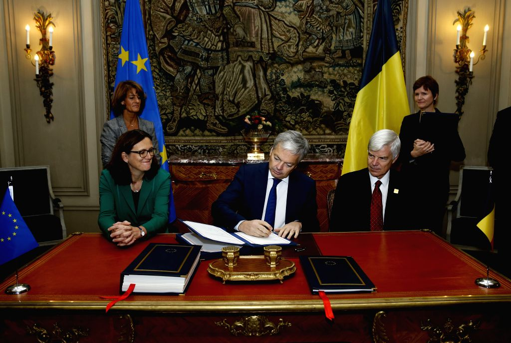 BRUSSELS, Oct. 29, 2016 - Belgian Deputy Prime Minister and Minister of Foreign Affairs Didier Reynders (C) signs an agreement with EU on Comprehensive Economic and Trade Agreement (CETA) between EU ...