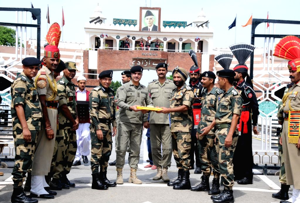BSF and Pakistani Rangers officials exchange sweets on Eid-ul-Fitr at Attari-Wagha border in Punjab on July 6, 2016.