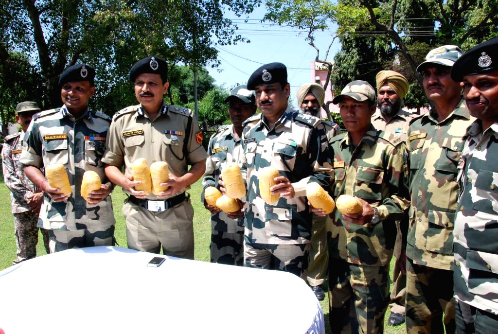 BSF personnel display 10 kg heroin recovered near the Pulmoran border outpost in Punjab on April 24, 2014.
