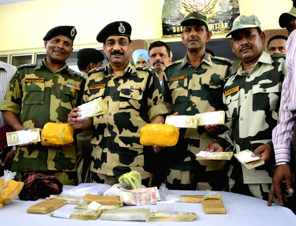 BSF personnel display 4 kg heroin and fake Indian currency notes with a face value of  7.83 Lakhs which were recovered by them in Amritsar sector on July 9, 2014.