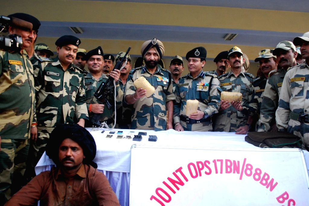 BSF personnel display before media the articles, including a US-made automatic gun, 24 cartridges and three mobile phones with Pakistani SIM cards, recovered from a Pakistani national who ...