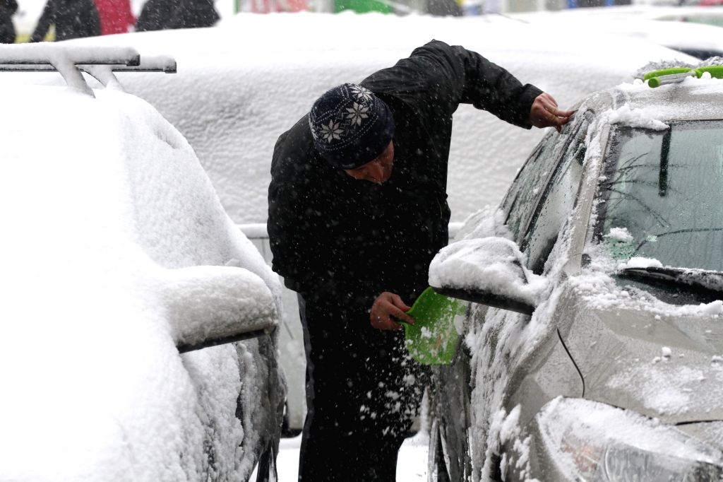 A man cleans his car in Bucharest, capital of Romania, Dec. 29, 2014. Romania's National Meteorology Administration on Monday issued a Code Red warning of ...
