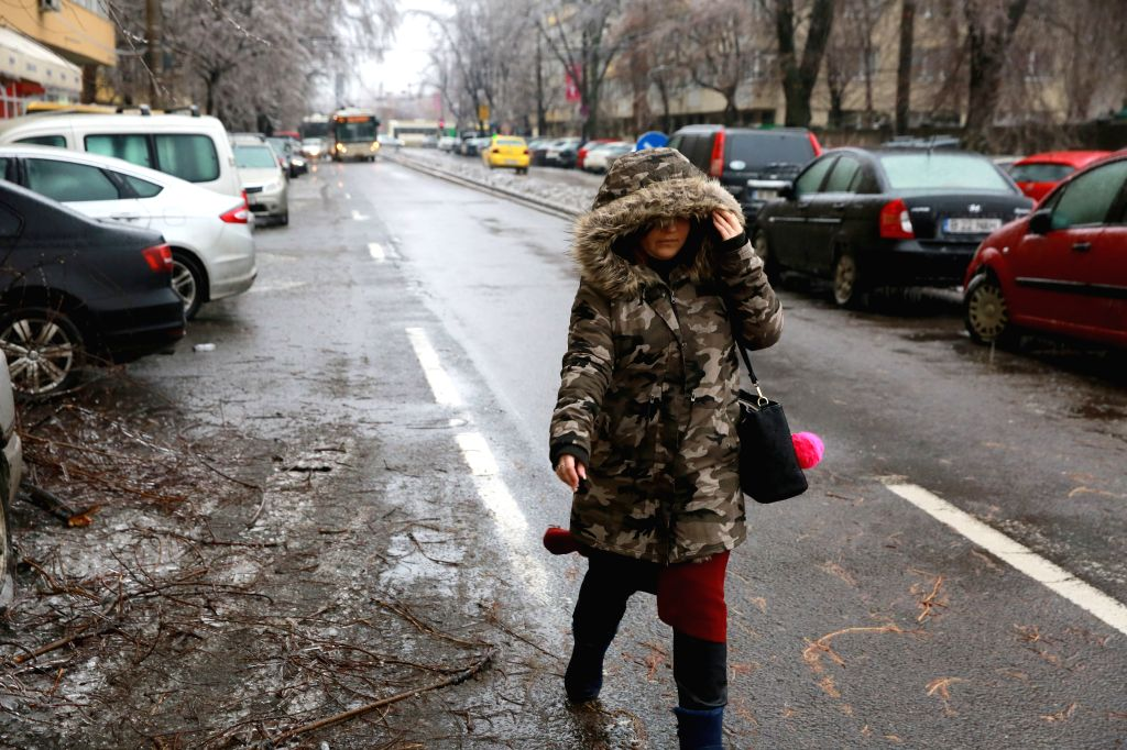 BUCHAREST, Jan. 26, 2019 - A pedestrian walks on a road covered with a glaze of ice in Bucharest, Romania, Jan. 26, 2019. The southern part of Romania is under an orange alert issued by meteorology ...