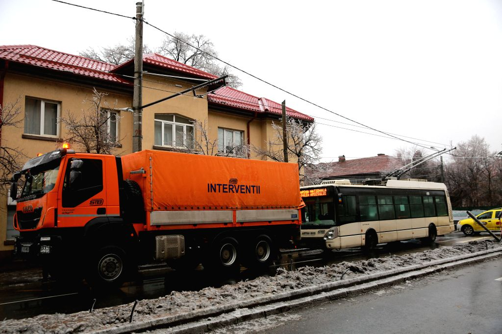 BUCHAREST, Jan. 26, 2019 - A trolleybus is pulled by an emergency intervention truck as power lines are covered with ice in Bucharest, Romania, Jan. 26, 2019. The southern part of Romania is under an ...