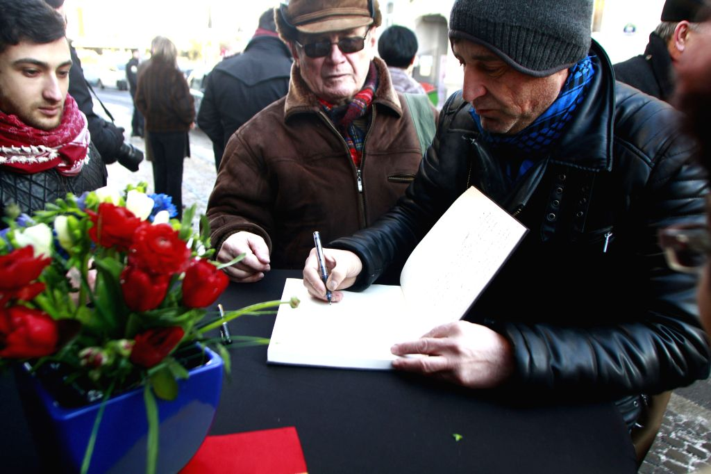 """A man signs on a book of condolence for the victims of the shooting at the office of the French magazine """"Charlie Hebdo"""", at the French Embassy in ..."""