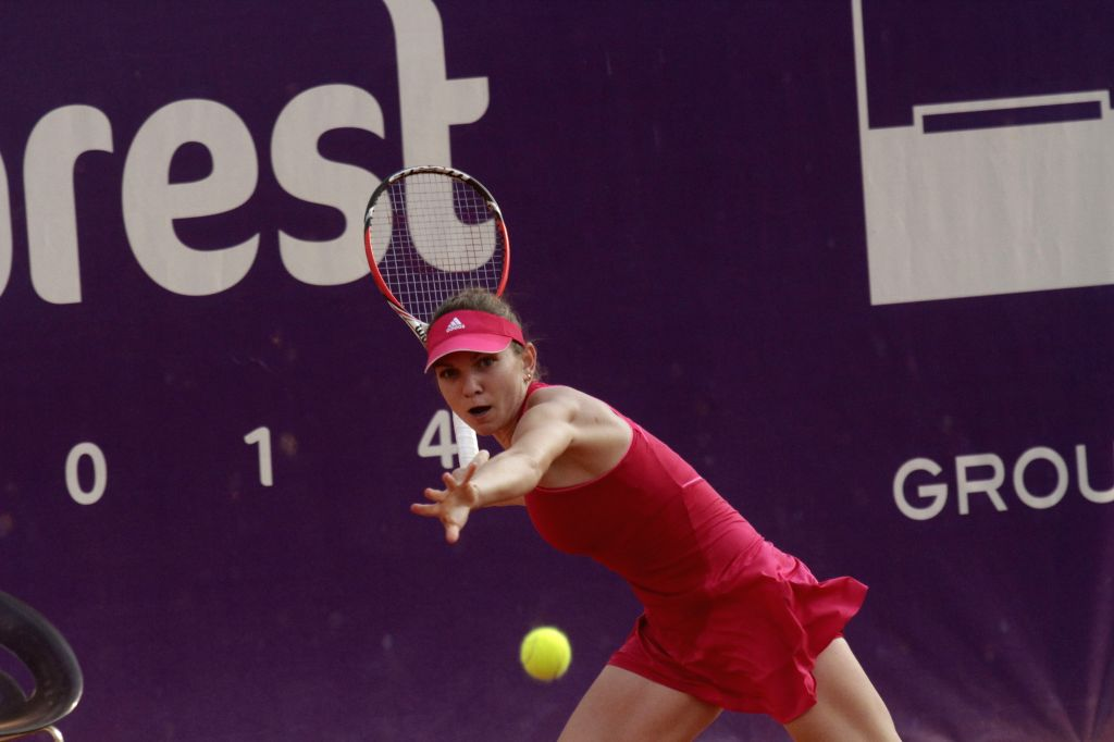 World No. 3 Simona Halep returns the ball during the women's singles match against Indy De Vroome of the Netherland at the 2014 Bucharest Open tennis tournament ..