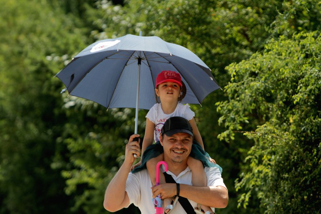 BUCHAREST, July 2, 2017 - A man protects a child and himself from the sun with an umbrella in Otopeni near Bucharest July 1, 2017. The highest temperature stood at 44 degrees Celsius in the east half ...
