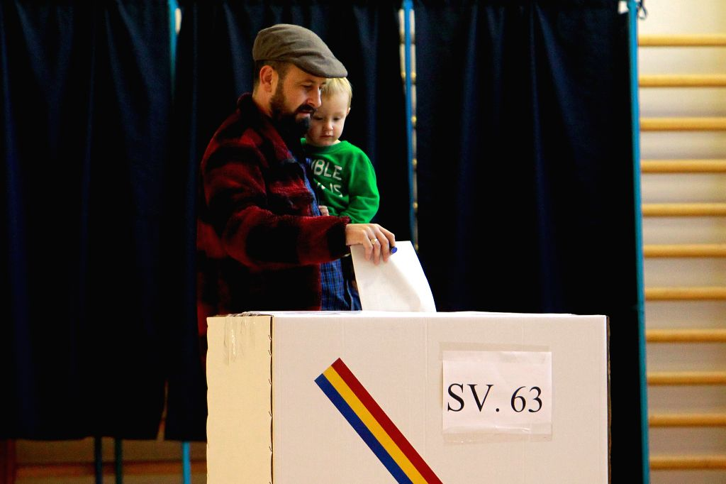 BUCHAREST, Nov. 10, 2019 - A Romanian man holds his child while voting at a polling station in Bucharest, Romania, Nov. 10, 2019. Romanian voters went to the polls on Sunday to elect a new president ...