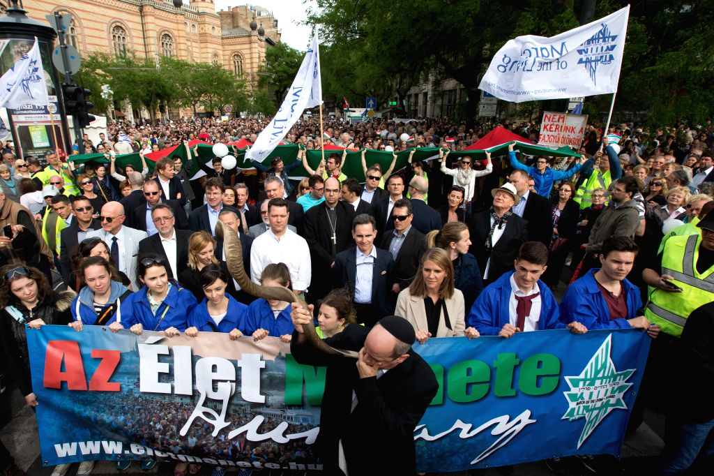 """BUDAPEST, April 17, 2016 - People attend the """"March of the Living"""" to commemorate the Hungarian victims of the Holocaust during World War II in Budapest, Hungary, April 17, 2016."""