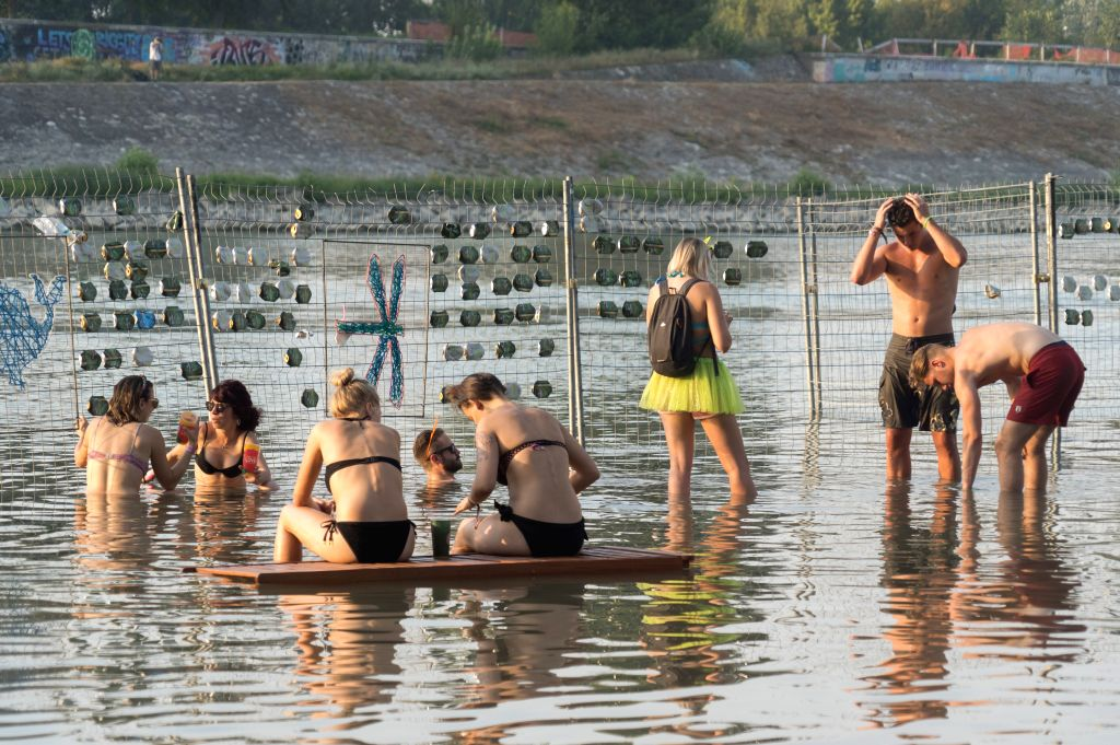BUDAPEST, Aug. 13, 2019 - People cool off in water on a riverside during the Sziget Festival in Budapest, Hungary, Aug. 12, 2019.