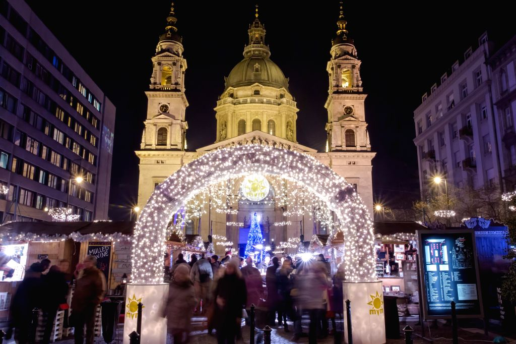 Photo taken on Dec. 11, 2014 shows a Christmas market decorated with led-lights in front of Saint Stephen Basilique in central Budapest, Hungary. (Xinhua/Attila ...