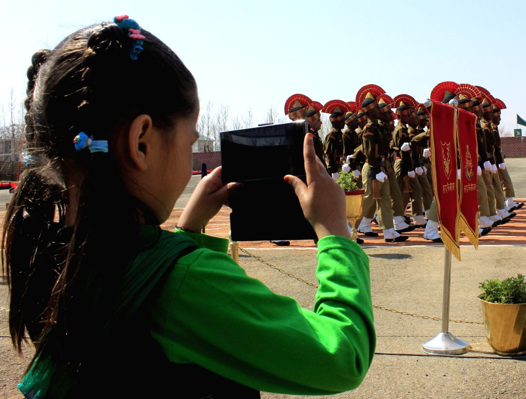 A young girl clicks pictures of the new recruits of the BSF during their passing out parade at Humhama Headquarters in Budgam district of Jammu and Kashmir on March 27, 2015.