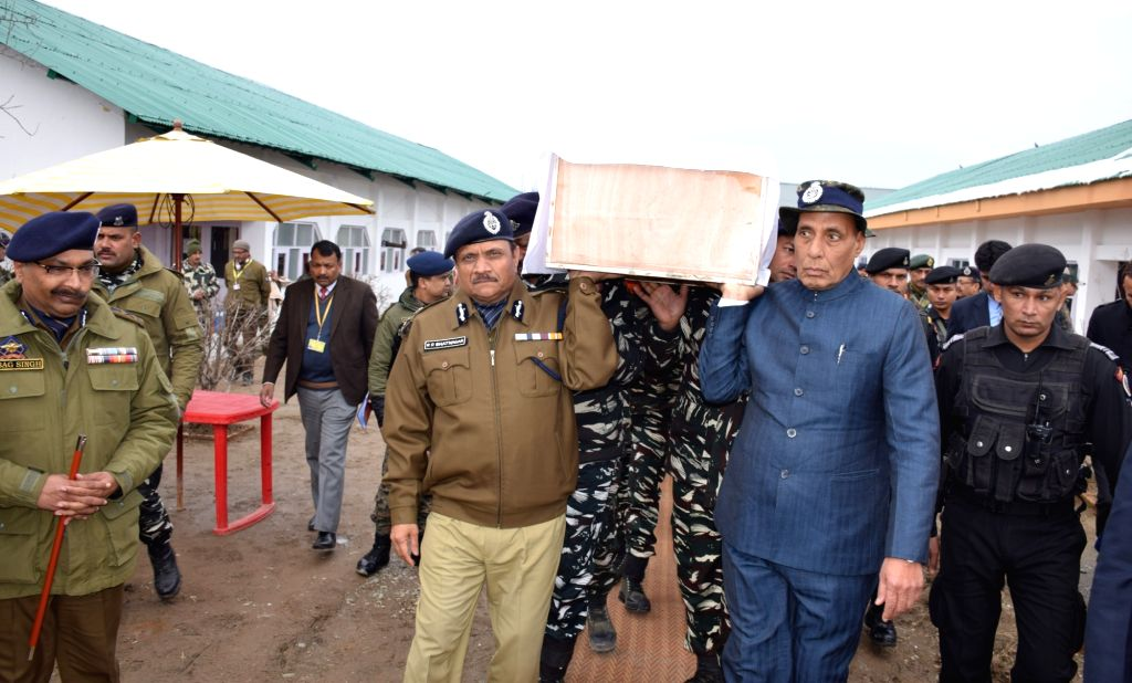 Budgam: Union Home Minister Rajnath Singh lifts the coffin of one of the one of the 45 CRPF personnel killed in a suicide attack by militants in Jammu and Kashmir's Pulwama district on 14th Feb 2019; in Budgam of Jammu and Kashmir, on Feb 15, 2019. ( - Rajnath Singh
