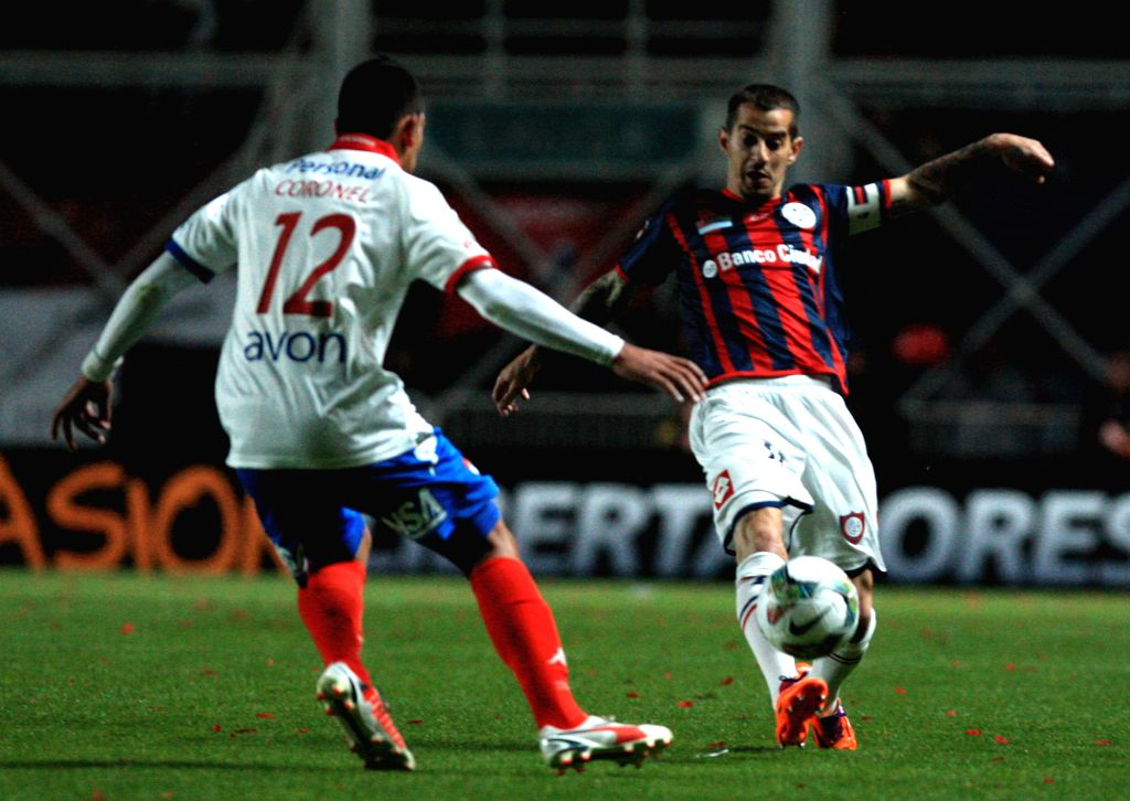 Leandro Romagnoli (R) of San Lorenzo vies for the ball with Nacional's Ramon Coronel (L), during their second leg final match of the 2014 Libertadores Cup, ...