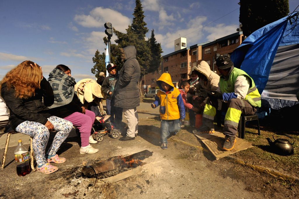 """People evicted from the """"Pope Francis"""" settlement, camp near the Villa Lugano neighborhood, in Buenos Aires, capital of Argentina, on Aug. 27, 2014. ."""