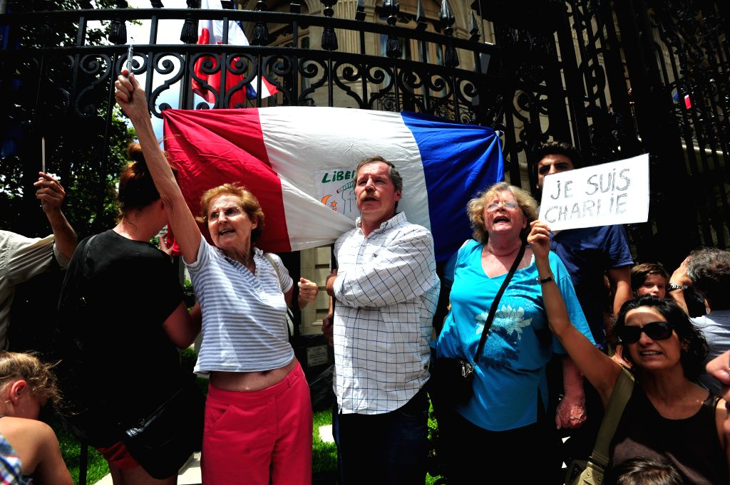 People take part in a rally in honor of the 17 victims killed during the three days deadly terrorist attack in France, in front of French Ambassy in Buenos ...