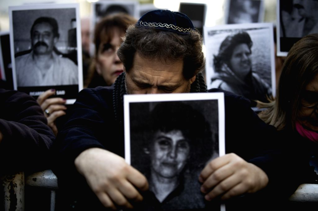 BUENOS AIRES, July 19, 2016 - A man holds a victim's picture during a commemoration of the 22nd anniversary of a terrorist attack on a Jewish center in 1994 in Buenos Aires, capital of Argentina, on ...