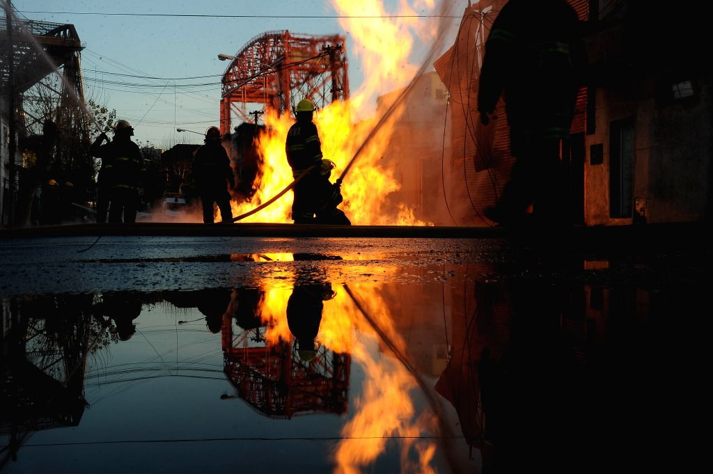 Firefighters try to douse a fire in a building near the Avellaneda bridge, in Buenos Aires, Argentina, on July 9, 2014. A fire occurred Wednesday in a building .