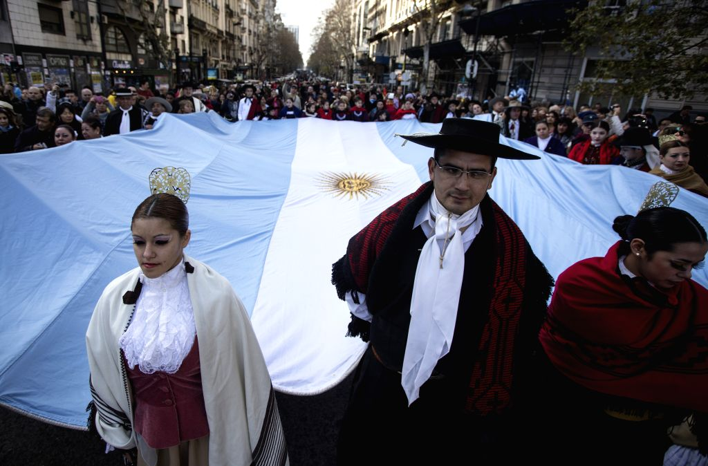 """Residents wearing traditional costumes take part in the parade for the celebration of Argentina's Independence Day, in the """"Avenida de Mayo"""", in ..."""