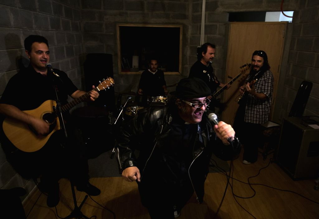 Argentine priest Cesar Scicchitano Tagle (front) and his band rehearse in his house in Buenos Aires, capital of Argentina, April 15, 2014. Besides his normal ...