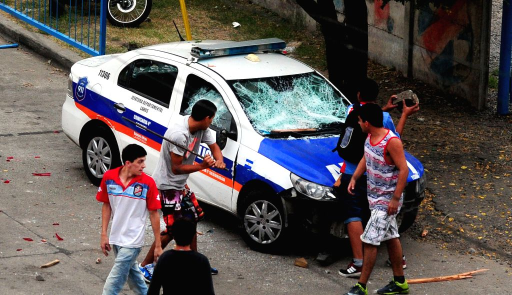 Fans hit a police vehicle in front of the Julio Humberto Grondona stadium, during the soccer match between Arsenal de Sarandi and Aldosivi, in Buenos Aires, ...