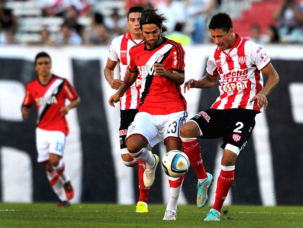 River Plate's Leonardo Ponzio (C) vies for the ball with Rolando Garcia of Union de Santa Fe during the match of the Argentinean soccer, held in the Monumental ...